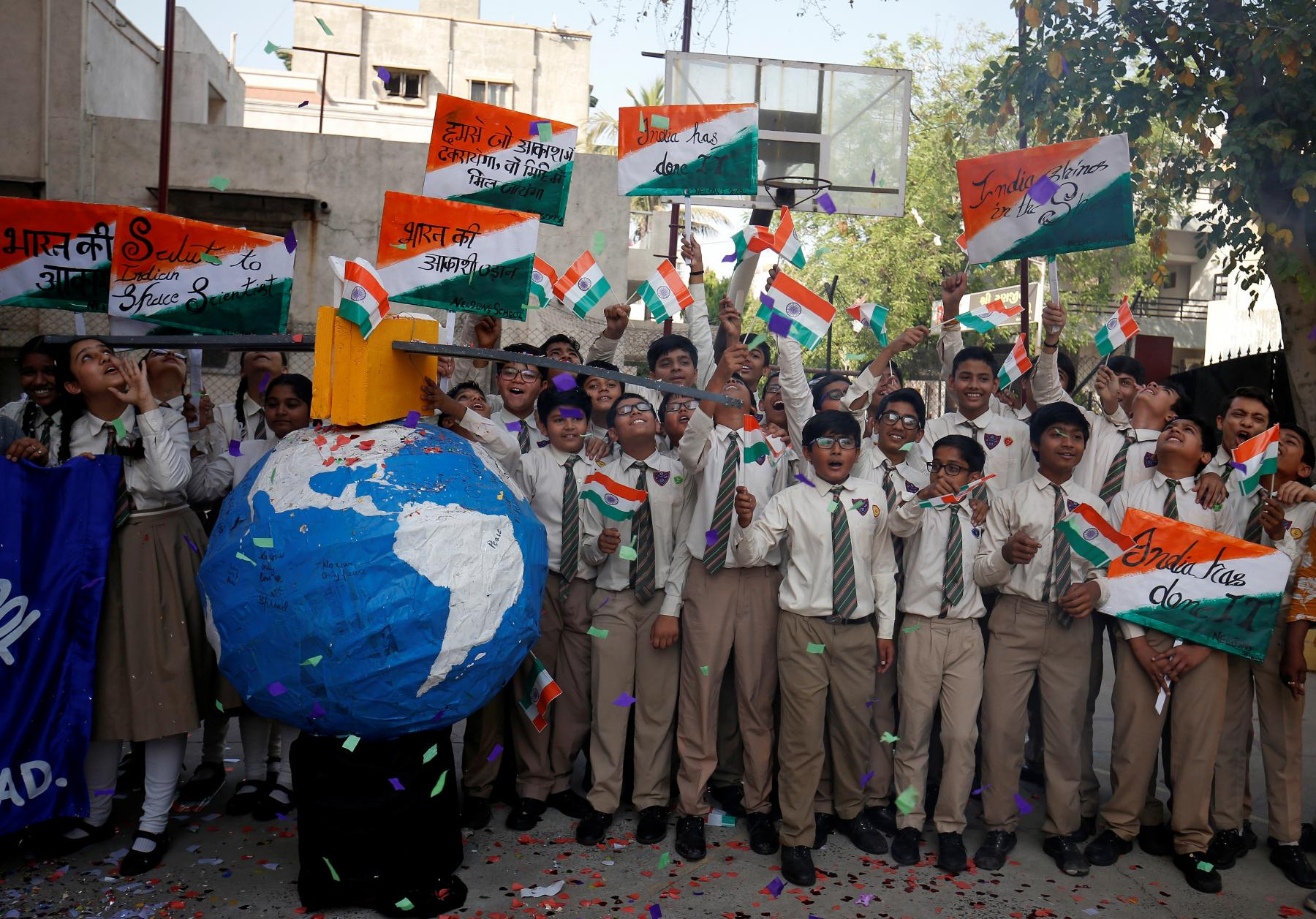 Students cheer and raise flags at a school in Ahmedabad after a successful anti-satellite missile test in India